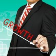 Businessman drawing a graph with Growth going down — Stock Photo #26152371