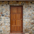 Wooden door on stoned house — Stock Photo #26154919