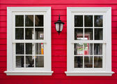 White windows with lamp on a red wooden house — Stock Photo