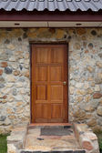 Wooden door on stoned house — Stockfoto