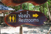 Restroom sign on wood board — Stock Photo