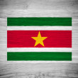 Suriname flag on wood texture — Stock Photo