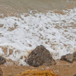 Foto Stock: Water swirling around beach rocks