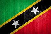 Saint Kitts and Nevis Flag on wood background — Stock Photo