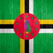 Постер, плакат: Dominica Flag on wood background