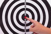 Hand point to bulls eye target — Stock Photo