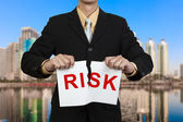 Businessman tear paper with word Risk in red — Stock Photo
