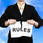 Постер, плакат: Businessman tear paper with word Rules
