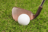 Golf ball on green grass with iron club — Stock Photo