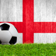 Soccer ball on grass with England flag background — Zdjęcie stockowe #42307077