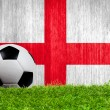Soccer ball on grass with England flag background — Stockfoto #42307077