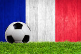 Soccer ball on grass with France flag background — Stock Photo