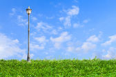 Streetlamp on artificial grass under blue sky — Stock Photo
