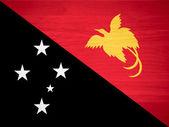 Papua New Guinea flag on wood texture — Stock Photo