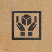 Hand handle package icon on paper box background — Stockfoto