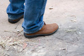 Human foot with brown leather shoes and jeans — Stock Photo