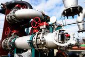 Průmyslová zóna, ocelové potrubí a ventily proti modré obloze — Stock fotografie