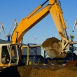 Hydraulic excavator at work. Shovel bucket and cranes against bl - Stock Photo