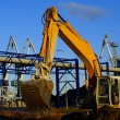 Hydraulic excavator at work. Shovel bucket against blue sky - Stock Photo