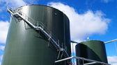 Industriële zone, stalen pijpleidingen en tanks tegen blauwe hemel — Stockfoto