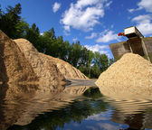 Storage of wooden biomass against blue sky with reflection — Stock Photo