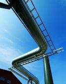Zona industriale, tubazioni in acciaio e valvole contro il cielo blu — Foto Stock