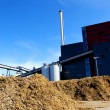 Stock Photo: Bio power plant with storage of wooden fuel against blue sky