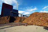 Bio power plant with storage of wooden fuel against blue sky — Stock Photo