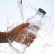 Water bottle in hand, in a spray of water droplets — Stock Photo