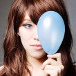 Portrait of middle aged woman blowing a balloon against a grunge — Stock Photo