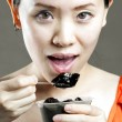 A beautiful woman eating food from a bowl — Stock Photo