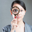 Portrait of lovely young woman with magnifying glass showing her — Stock Photo #14035797