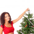 Beautiful african woman decorating Christmas tree — Stock Photo #18576581