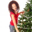 Beautiful african woman decorating Christmas tree - Stock Photo