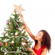 Beautiful african woman decorating Christmas tree — Stock Photo #18576687