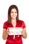 Beautiful woman holding presents while smiling — Stockfoto