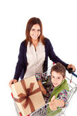 Happy mother with her kid sitting in shopping basket — Stock Photo