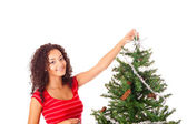 Beautiful african woman decorating Christmas tree — Stock Photo