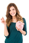 Casual woman looking to save money in a piggy bank — Stock Photo