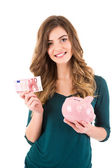 Casual woman looking to save money in a piggy bank — Foto de Stock
