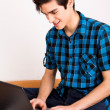 Young man working on computer laptop at home — Stock Photo