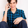 Young man talking on the phone at home — Stock Photo