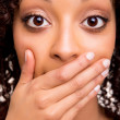 Surprised young african woman with hands over her mouth — Stock Photo #26006029