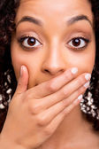 Surprised young african woman with hands over her mouth — Stock Photo