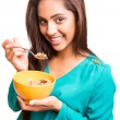 Beautiful mix race woman eating cereals — Stock Photo