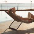 Stock Photo: Beautiful girl lying on sun lounger