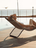 Beautiful girl lying on a sun lounger — Stock Photo
