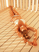 Girl lying in the beach pergola — Stock Photo