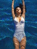 Girl relaxing in swimming pool — Stock Photo