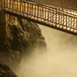Narrow wooden steel bridge over the wild river and rocks at night — Stock Photo